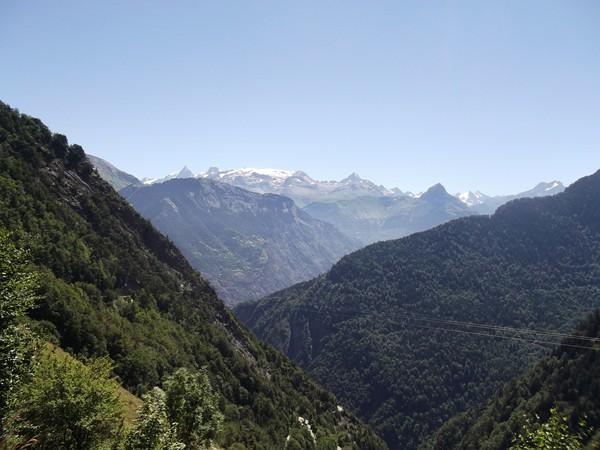 En se retournant, on peut voir la route de Villard-Reculas et an arrière-plan le Massif des Ecrins avec la pointe de La Meije sur la gauche.