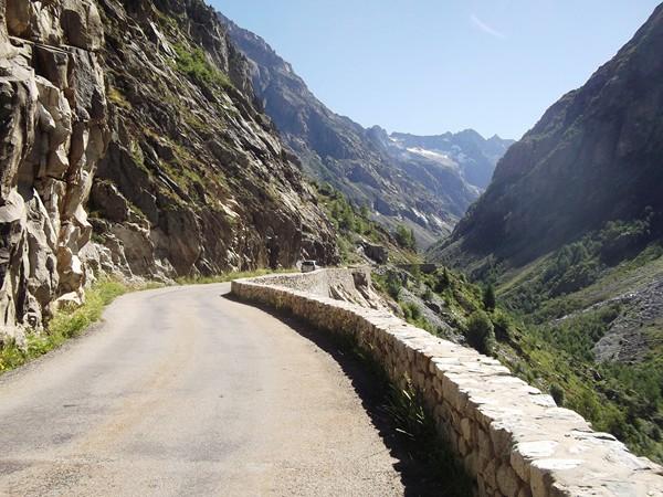 Route buccolique, un parapet borde le ravin à droite.